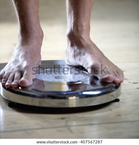 A young man standing on scales - stock photo