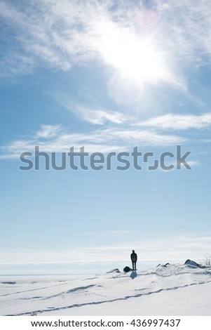 A young man stands alone in a snowy area - stock photo