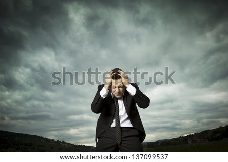 A young man stands in a valley between mountain ranges. Elegant and handsome. It looks downcast. Experiencing failure in solitude and isolation. - stock photo