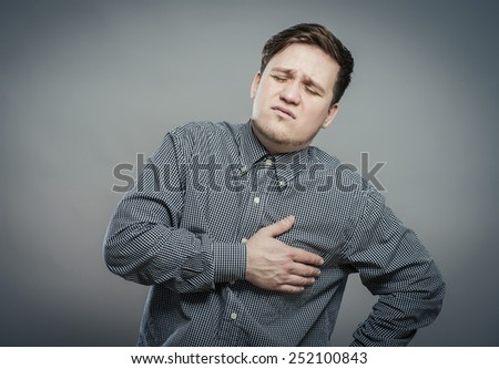 A young man suffering from heart pain - stock photo