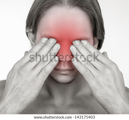 A young man suffering from pain in the eyes. Isolated on white background - stock photo