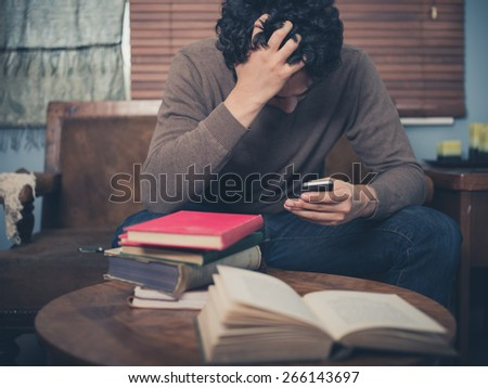 A young man surrounded by books is sitting on a sofa and is looking upset as he is using his smartphone - stock photo