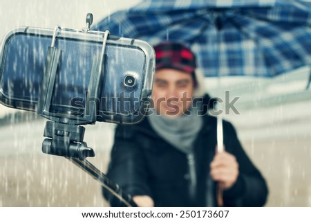 a young man taking a self-portrait with a selfie-stick under the rain - stock photo