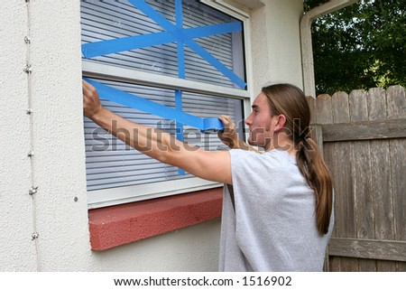 A young man taping windows on his home in preparation for a hurricane. - stock photo