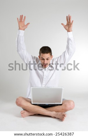 A young man throws his hands in the air surprised and delighted by what he had won while viewing the internet on a laptop computer. - stock photo