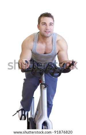 A young man training on an exercise bike at the gym - stock photo