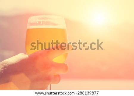 A young man tries to beer in the early morning on the beach - stock photo