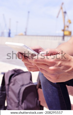 a young man using a tablet or an e-book outdoors - stock photo