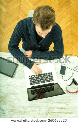 A young man using his laptop computer at home.	  - stock photo