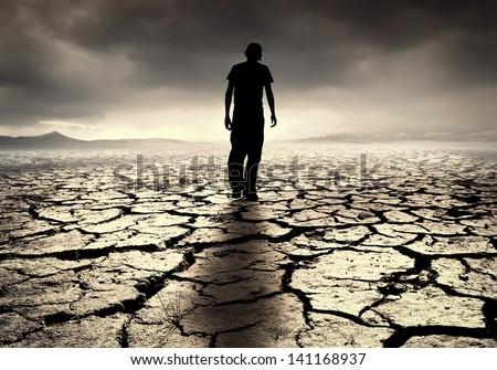 A young man walks into the desolate desert - stock photo