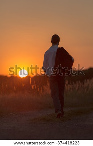 A young man walks lonely in a sundown - stock photo