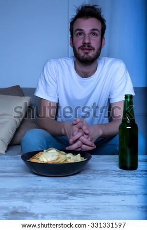 A young man watching a movie at nighttime with potato chips and beer at home in the living room.