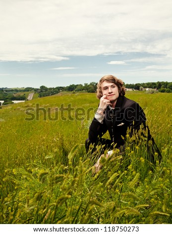 A young man wearing business attire kneeling in the tall grass. - stock photo