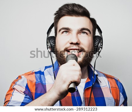 A young man with a beard wearing a shirt holding a microphone and singing, hipsterstyle.Over gray background. - stock photo