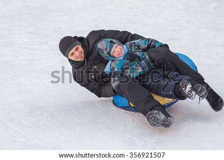 A young man with a cheerful boy with a roller coaster ride in the winter on the ice. Handsome Dad and son laughing in a winter park. Happy family playing with snow. - stock photo