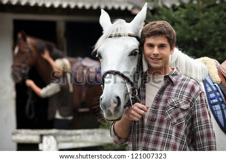 A young man with a horse. - stock photo