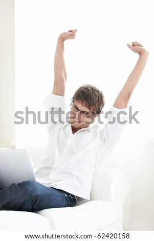 A young man with a laptop at home against the window - stock photo