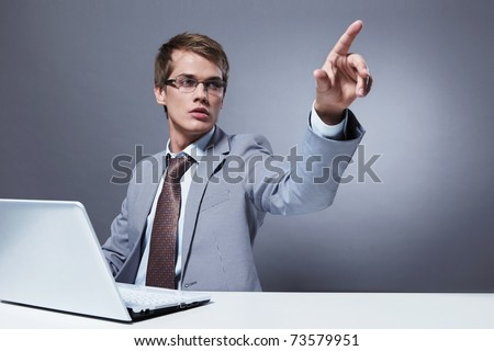 A young man with a laptop clicks on an invisible button - stock photo