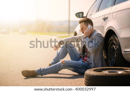 A young man with a silver car that broke down on the road.He is waiting for the technician to arrive. - stock photo