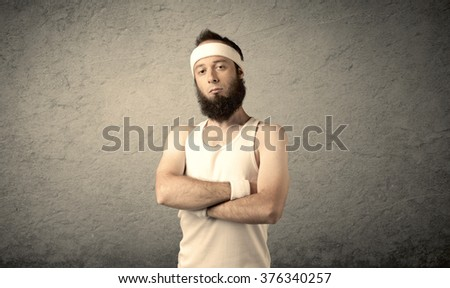 A young man with beard, headstrap and glasses posing in front of blank grey wall background, imagining he has big muscles - stock photo