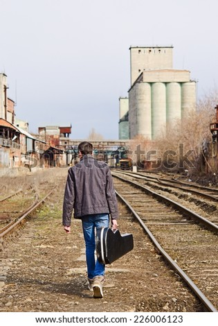 A young man with guitar case in hand going away by rails. Rear view - stock photo