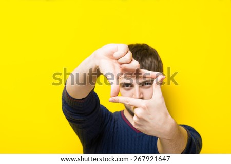 a young man with his hands on a yellow background frame - stock photo