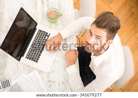 A young man working at home with a Laptop computer. - stock photo