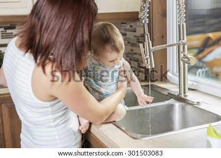 A Young mother and her adorable toddler daughter in kitchen - stock photo