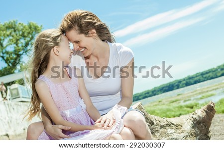 A Young mother and her young daughter fun time together outdoors. - stock photo