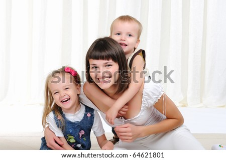 A young mother, her daughter and son having fun together - stock photo