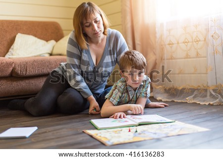 A young mother is engaged in training young son. - stock photo