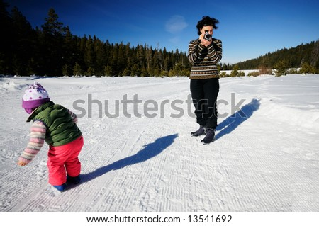 A young mother is filming her two year old daughter playing in the snow at the cross country ski resort in Sierra Nevada mountains in the vicinity of lake Tahoe, California. - stock photo