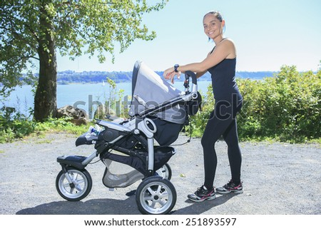 A Young mother jogging with a baby buggy - stock photo