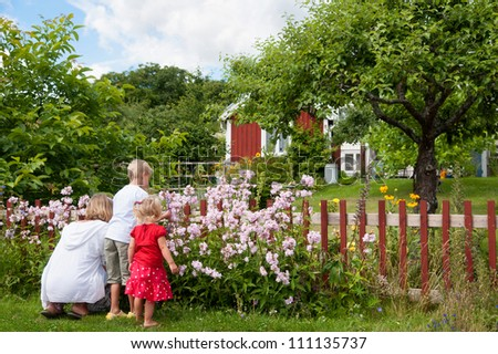 A young mother kneels on the grass with her two young children picking flowers in a beautiful lush rural garden with a house in the distance - stock photo
