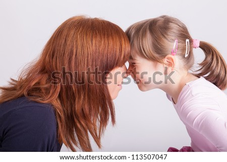 A young mother neck and neck with her daughter - stock photo