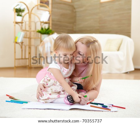 a young mother playing with her little baby at home - stock photo