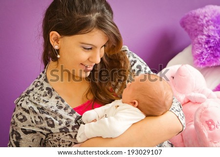 A young mother'??s special bonding moment with her newborn baby - stock photo