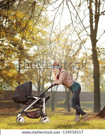 A young mother with a baby carriage walking in a park - stock photo