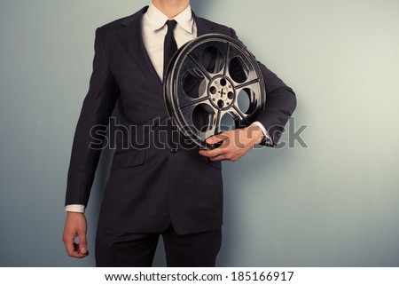 A young movie executive is holding an old film reel - stock photo