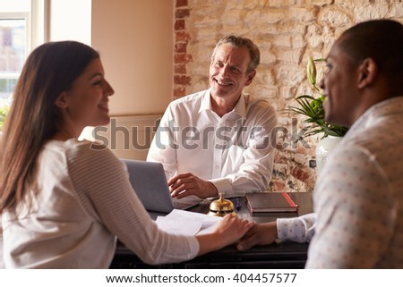 A young multi ethnic couple checking in at a hotel, close up - stock photo