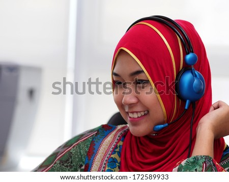 A young Muslim lady with a head set. - stock photo