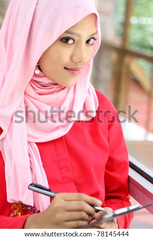 A young muslim woman holding report file while looking at camera - stock photo