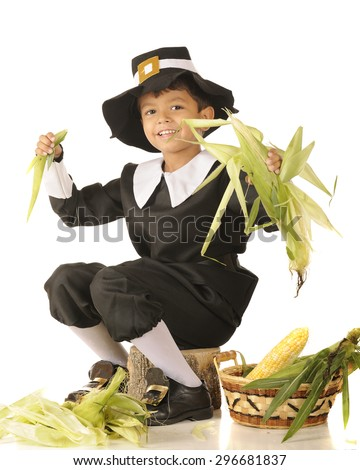 A young Pilgrim boy happily husking corn.  One a white background. - stock photo