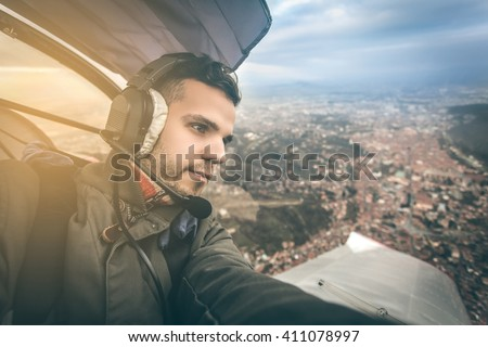 a young pilot in sightseeing flight above Brasov city having best conditions for flying - stock photo