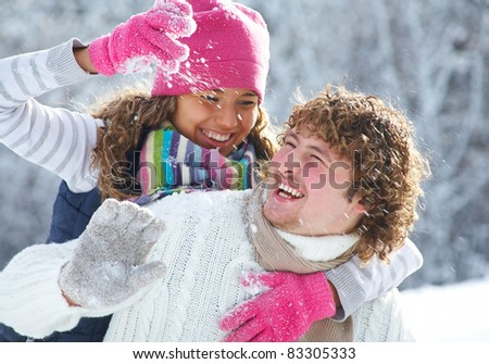 A young playful couple has a fun winter time in a snow park - stock photo