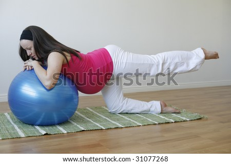 A young pregnant woman in a pink shirt doing a buttock and leg muscle exercise using a blue fitness ball. - stock photo