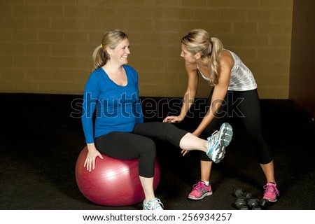 A young pregnant woman stretching with an atletic female trainer at the gym. - stock photo
