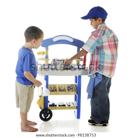 A young preschooler making a purchase from an older preschooler's candy stand.  Stand signs left blank for your text.  On a white background. - stock photo