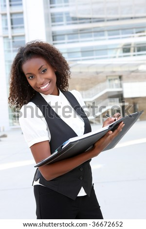 A young pretty african american business woman at office with binder - stock photo