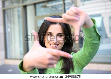 A young pretty business woman outside office building framing face - stock photo